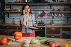 Vrolijke aardige vrouwentribune in keuken en bespreking op telefoon Zij glimlacht De pan van de vrouwengreep met voedsel Groenten royalty-vrije stock foto