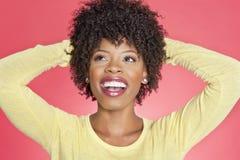 Vrolijke Afrikaanse Amerikaan die omhoog met handen achter hoofd over gekleurde achtergrond kijken Stock Foto's