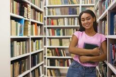 Vrolijke Afrikaanse Amerikaanse studente die zich bij boekenrekken bevinden stock foto's