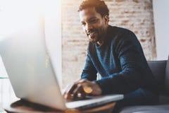 Vrolijke Afrikaanse mens gebruikend computer en glimlachend terwijl het zitten op de bank Concept jonge bedrijfsmensen die werken