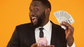 Vrolijke Afro-Amerikaanse mens in het spaarvarken van de kostuumholding en dollars, het crowdfunding stock footage