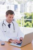 Vrolijke arts die aan laptop werken Royalty-vrije Stock Foto