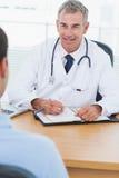 Vrolijke arts die drug voorschrijft aan zijn patiënt Royalty-vrije Stock Foto's