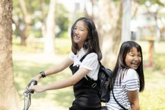 Vrolijke Aziatische de emotie berijdende fiets van het tienergeluk in publ stock foto
