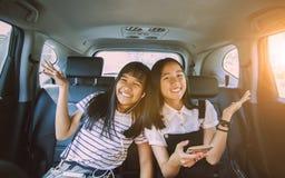 Vrolijke Aziatische de emotiezitting van het tienergeluk in personenauto stock afbeelding
