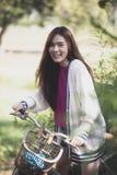 Vrolijke Aziatische jongere vrouw die op retro fiets in groen park berijden royalty-vrije stock afbeelding