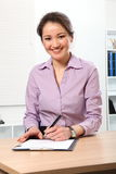Vrolijke Aziatische vrouw die op document op het werk schrijft Royalty-vrije Stock Fotografie