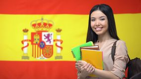 Vrolijke Aziatische vrouwelijke student die zich tegen Spaanse vlag, taal het bestuderen bevinden stock video