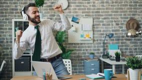 Vrolijke beambte die aan muziek in hoofdtelefoons luisteren die in werkplaats dansen stock videobeelden