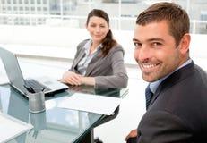 Vrolijke bedrijfsmensen die aan laptop werken Stock Foto