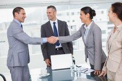 Vrolijke bedrijfsmensen die en handen ontmoeten schudden Stock Foto's