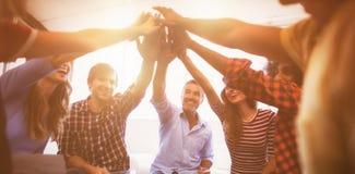 Vrolijke bedrijfsmensen die hoogte vijf geven terwijl het zitten van creatief bureau