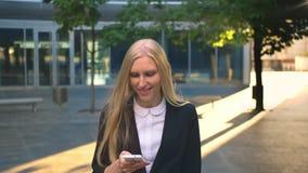 Vrolijke bedrijfsvrouw met telefoon in openlucht Tevreden blonde vrouw in zwarte jasjeholding smartphone en weg het kijken stock videobeelden