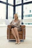 Vrolijke bedrijfsvrouwenzitting als voorzitter Binnen het werken aan laptop royalty-vrije stock foto's