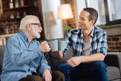 Vrolijke bejaarde clinking kop theeën met zijn zoon royalty-vrije stock afbeelding