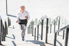 Vrolijke bejaarde dame die concrete stappen in openlucht lanceren Stock Afbeeldingen