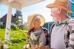 Vrolijke bejaarde dame die terwijl het bekijken haar houdende van gevende echtgenoot glimlachen royalty-vrije stock fotografie