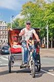Vrolijke bestuurder op zijn ontzagwekkende fietstaxi, Amsterdam, Nederland Stock Afbeelding