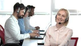 Vrolijke blonde dame in call centre die een cliënt raadplegen stock videobeelden