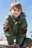 Vrolijke blonde jongen bij speelplaats stock afbeeldingen