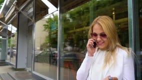 Vrolijke blondevrouw in modieuze uitrusting die op telefoon op de straat spreken stock videobeelden