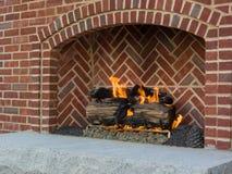 Vrolijke brandbrandwonden in baksteenopen haard die openluchtruimte verwarmen stock afbeeldingen