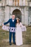 Vrolijke bruid en bruidegom die de artistieke brieven van de papercutliefde houden Stock Foto's