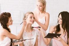 Vrolijke bruidsmeisjes die klaar de bruid helpen te worden Royalty-vrije Stock Foto
