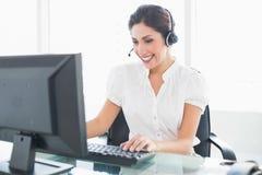 Vrolijke call centreagent die bij haar bureau aan een vraag werken Stock Afbeeldingen