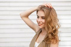 Vrolijke charmante jonge vrouw met een prachtige glimlach met krullend blond haar in het modieuze vest stellen royalty-vrije stock afbeeldingen