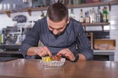 Vrolijke chef-kok in eenvormig, opmakend een heerlijke hamburger met gebraden aardappels in de mand Royalty-vrije Stock Afbeelding