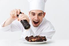 Vrolijke chef-kokkok die eenvormige peper dragen stock afbeeldingen