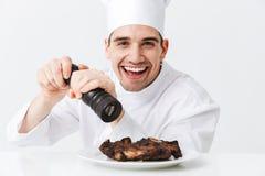 Vrolijke chef-kokkok die eenvormige peper dragen stock foto