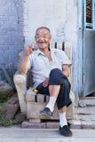 Vrolijke Chinese oudste op een oude stoel voor zijn huis, Peking, China Stock Fotografie