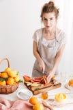 Vrolijke dame die zich dichtbij lijst met heel wat citrusvruchten bevinden Royalty-vrije Stock Foto's