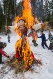 Vrolijke dans rond het brandende beeltenis van Maslenitsa, op 13 Maart Stock Afbeeldingen