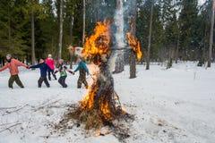 Vrolijke dans rond het brandende beeltenis van Maslenitsa, op 13 Maart Stock Afbeelding