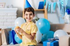 Vrolijke de verjaardag van de jongensholding muffin en het glimlachen Royalty-vrije Stock Foto