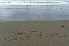 Vrolijke die Kerstmis in het zand met nat erachter zand wordt geschreven stock afbeelding