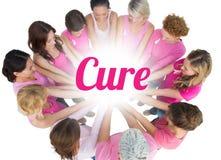 Vrolijke die vrouwen in een cirkel worden aangesloten bij die roze voor borstkanker dragen Stock Foto's