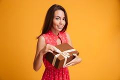 Vrolijke donkerbruine vrouw in de gift van de kledingsholding Royalty-vrije Stock Fotografie