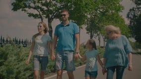 Vrolijke drie generatiefamilie die in openlucht lopen stock video