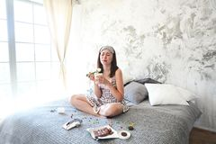 Vrolijke droevige jonge craing vrouw die snoepjes in haar slaapkamer eten stock foto