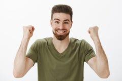 Vrolijke en geactiveerde actieve leuke mannelijke ventilator met baard in t-shirt die dichtgeklemde vuisten in overwinning en tri stock fotografie