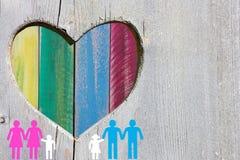 Vrolijke en lesbische families op houten achtergrond met veelkleurig regenbooghart stock foto's