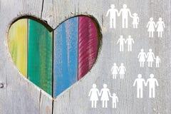 Vrolijke en lesbische paren en families op houten achtergrond met veelkleurig regenbooghart stock afbeelding