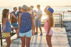 Vrolijke en onbezorgde groep vrienden die uit bij de zonnige de zomerkust hangen op hun vakantie royalty-vrije stock foto's