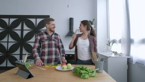 Vrolijke familie, aantrekkelijke vrouw met echtgenoot het dansen en het hebben van pret terwijl het koken van gezonde maaltijd va stock video