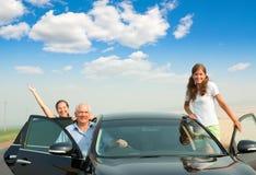 Vrolijke familie in de zwarte auto royalty-vrije stock afbeelding