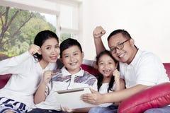 Vrolijke familie die een digitale tablet op bank gebruiken Stock Foto's